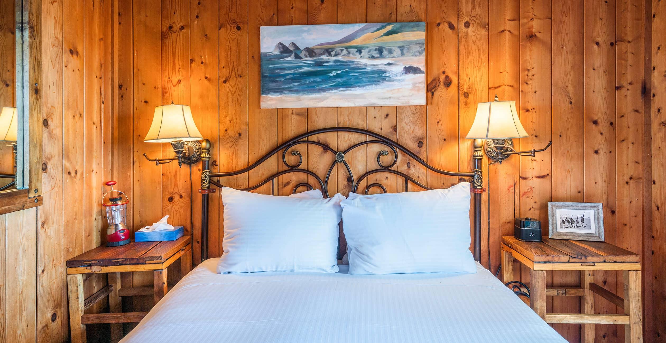 Bed between warm lamps in Cabin 3 bedroom