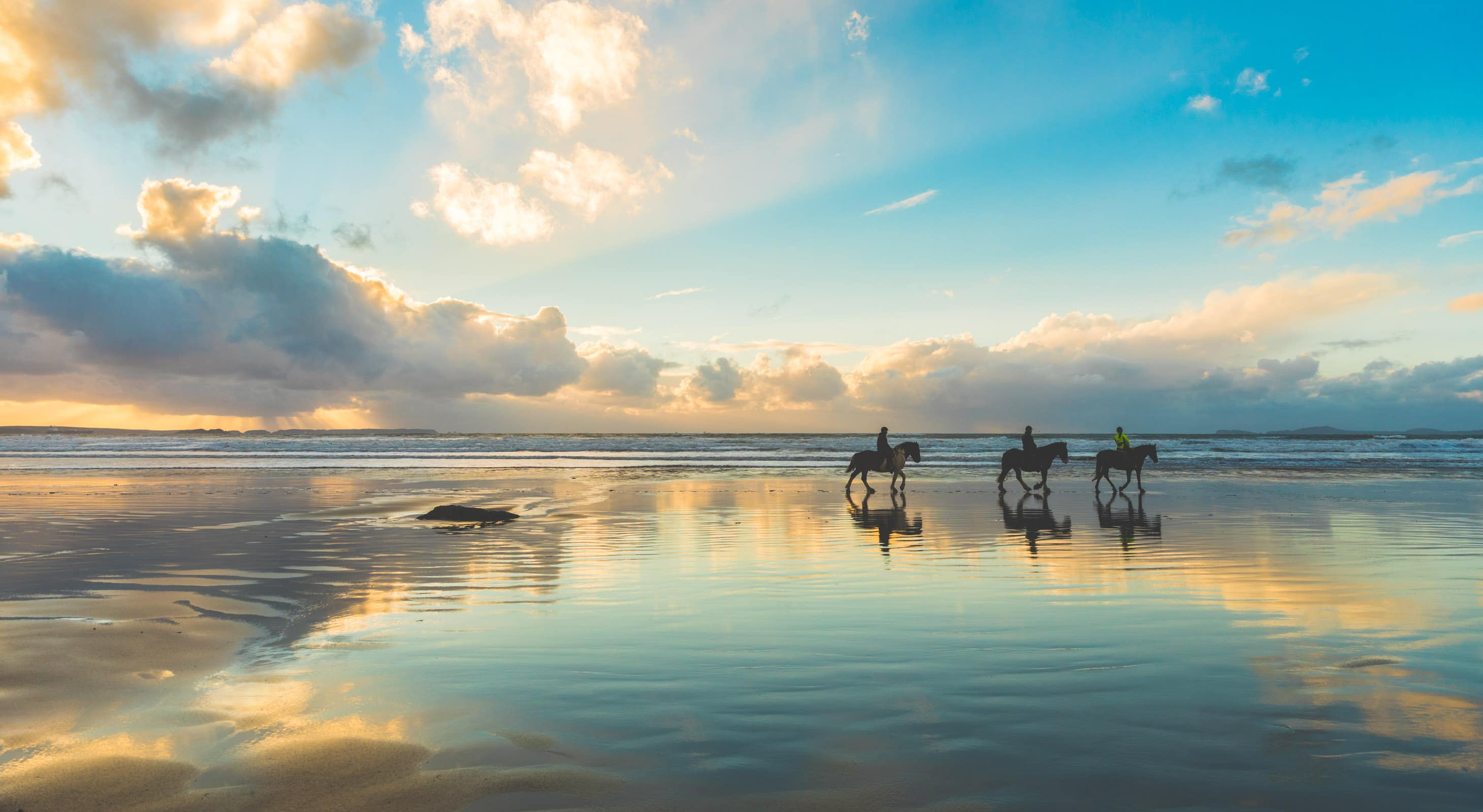 Group riding horseback on the beach at sunset
