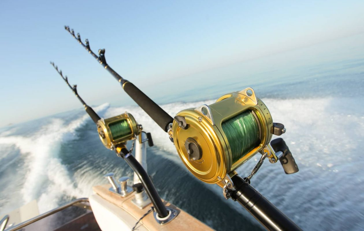 Two large fishing poles on the edge of a sport fishing boat