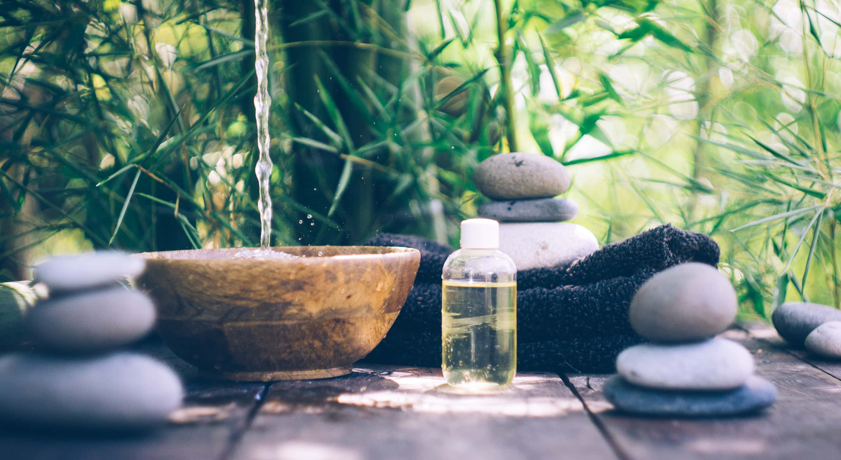 A zen spa scene with a wooden bowl, massage oil, and stacked pebbles near bamboo
