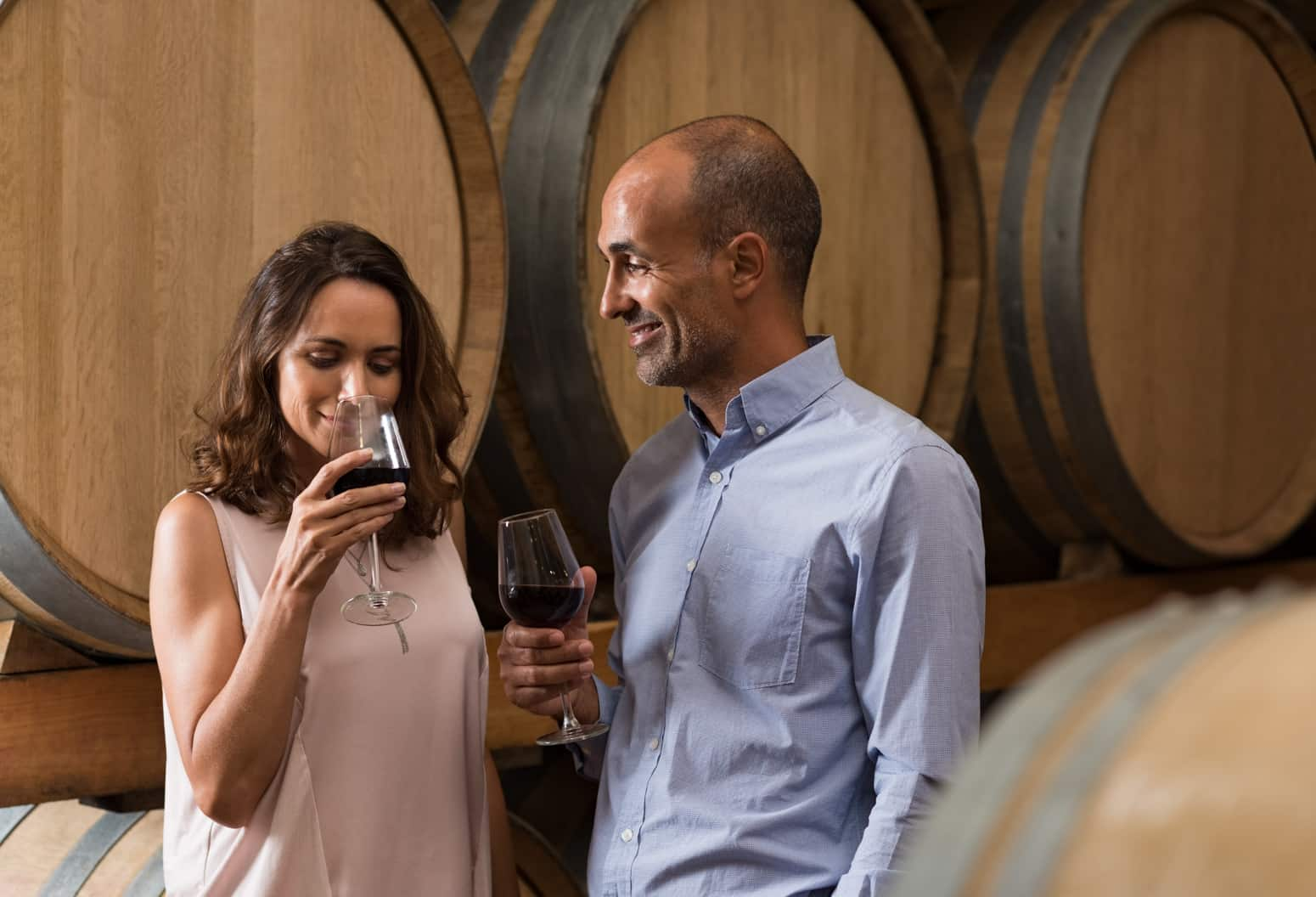 A woman and Man tasting wine in front of wine casks
