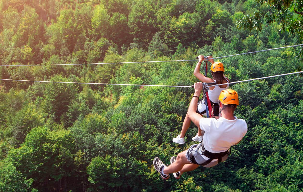 A couple ziplining outdoors