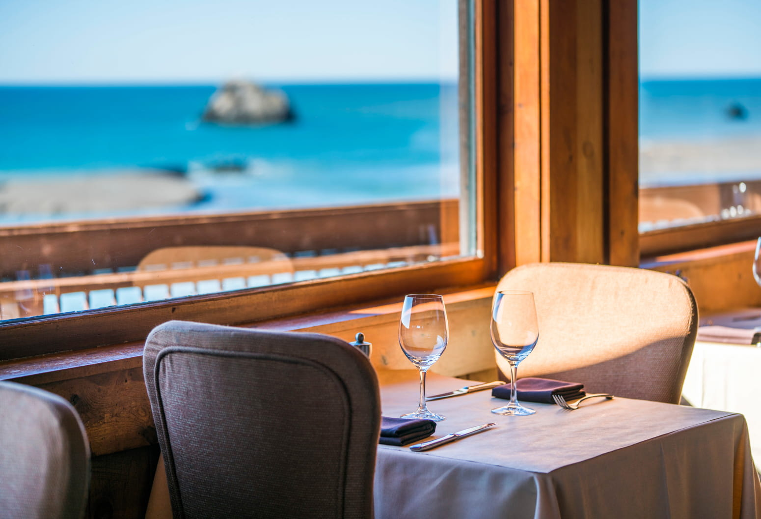 Intimate seating for two near a large window overlooking the Pacific Ocean
