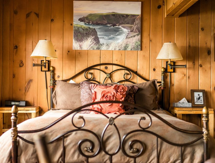 Queen bed in a cabin with wooden panel walls