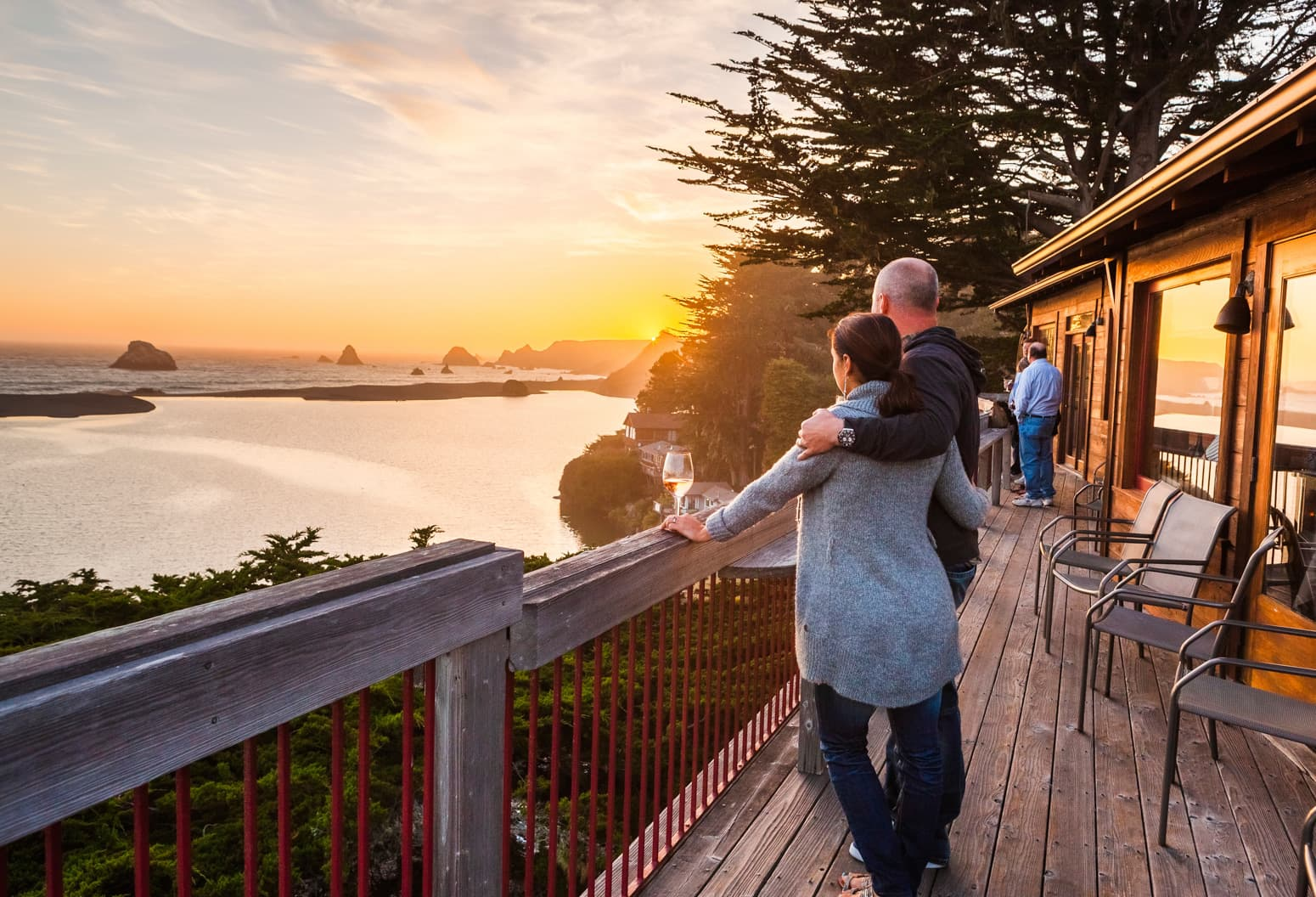 Couple watches sunset with drinks at River's End Restaurant