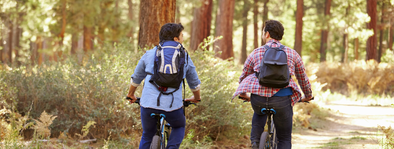 Two gay men biking in the forest